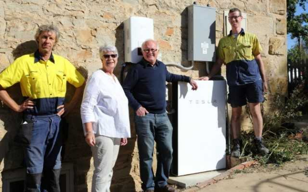 John and Bev Tozer, MASH customers in Castlemaine with their newly installed Tesla Powerwall battery, and installers Morgan Kurrajong and Alex Orr. Image: courtesy MASH (More Australian Solar Homes)