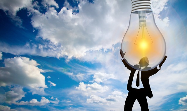 Clean energy access illustrated by man holding light bulb in the sky